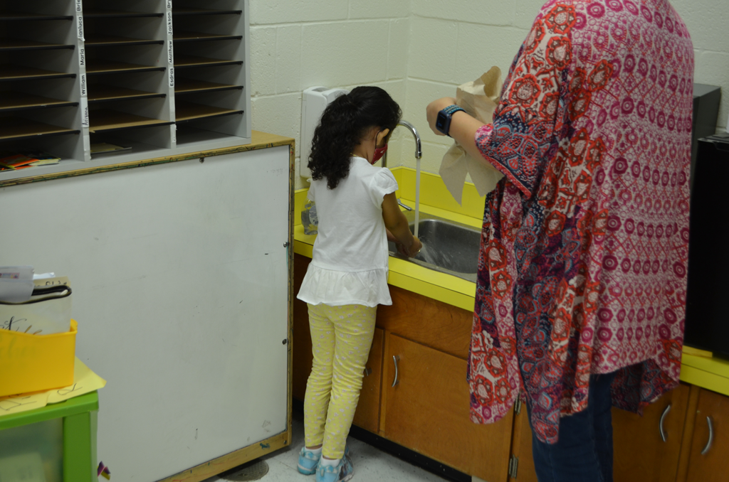 Student washing their hands.